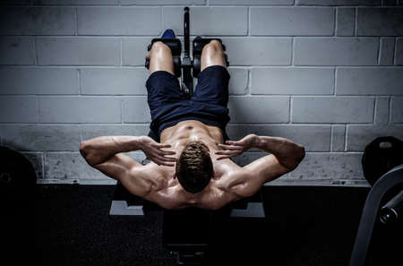 levantar peso: Hombre muscular que hace ejercicios de abdominales en el estudio del Gimnasio