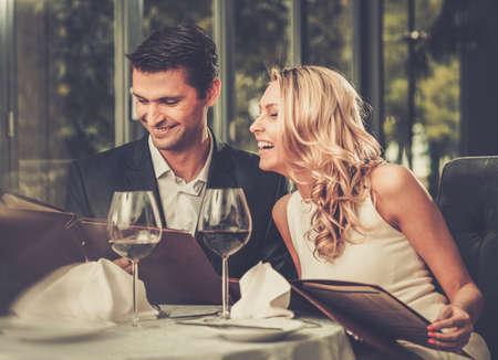 casal: Pares alegres com menu em um restaurante