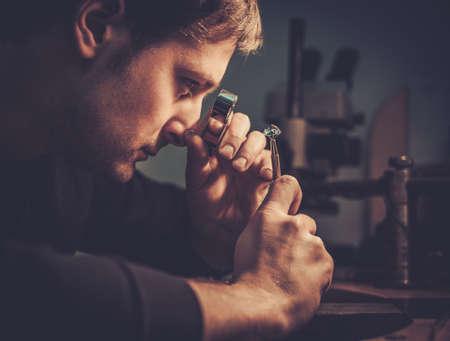 Bijoutier regardant l'anneau à travers un microscope dans un atelier. Banque d'images