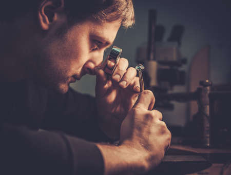 perlas: Joyero mirando el anillo a través de microscopio en un taller.