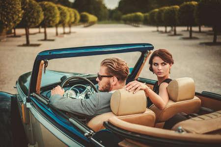 lifestyle: Pareja rica en un convertible clásico