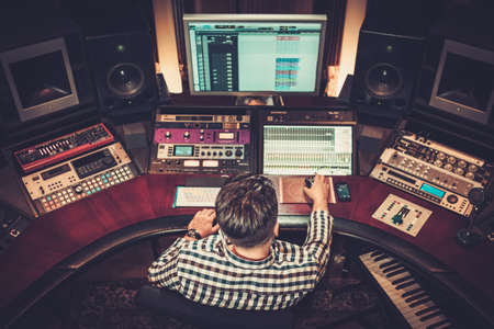 audio mixer: Sound engineer working at mixing panel in the boutique recording studio. Stock Photo