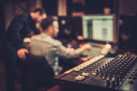 audio mixer: Sound engineer and producer working together at mixing panel in the boutique recording studio. Stock Photo