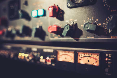 recording studio: Close-up amplifier equipment with sliders and knobs at boutique recording studio.