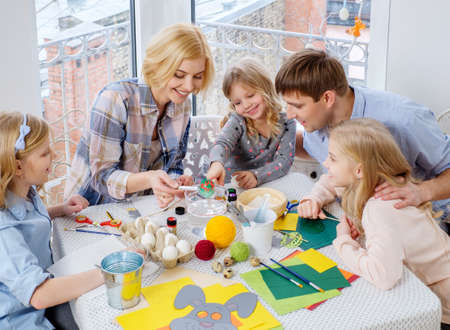 decorating: Cheerful family having fun painting and decorating easter eggs.