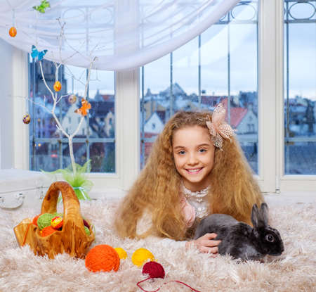 room decoration: Beautiful little girl lying on carpet and playing with cute bunny. Stock Photo