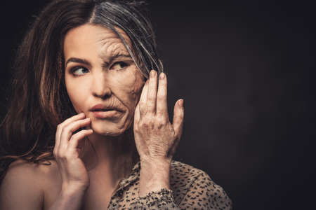 aging woman: Aging and skin care concept. Half old half young woman.