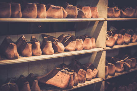 metier: Various of vintage wooden shoe lasts in a row on the old shelves.