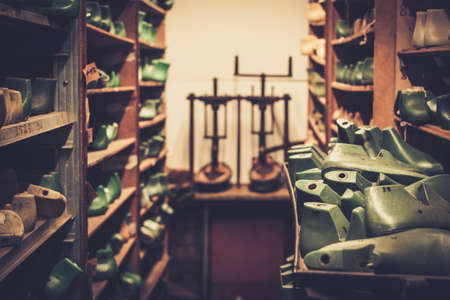shoe model: Various of vintage wooden shoe lasts in a row on the old shelves.