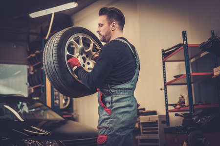 tire fitting: Professional car  mechanic balancing car wheel on balancer in auto repair service.
