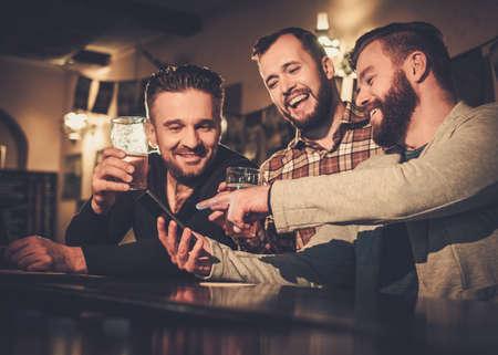 barra: Alegres viejos amigos que se divierten con el tel�fono inteligente y beber cerveza de barril en barra de bar en bar.