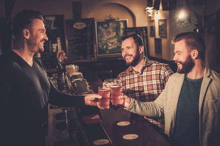bachelor: Cheerful old friends having fun and drinking draft beer at bar counter in pub. Stock Photo