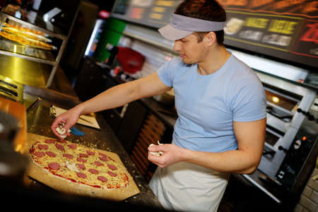 italian sausage: Handsome pizzaiolo making pizza at kitchen in pizzeria.