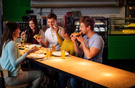 personas comiendo: amigos multirraciales alegres que se divierten comiendo pizza en una pizzería. Foto de archivo