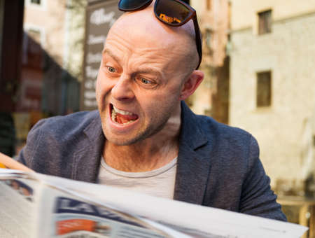 enraged: MIddle-aged man becoming enraged while reading newspaper outdoors