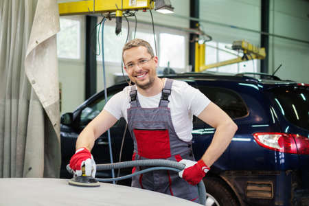 priming paint: Cheerful serviceman performing grinding with machine on a car bonnet in a workshop Stock Photo
