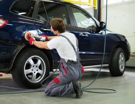 body paint: Serviceman pulido carrocer�a con la m�quina en un taller Foto de archivo