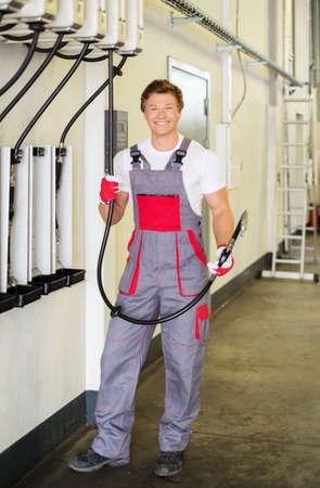 unbottled: Cheerful serviceman holding hose with unbottled motor oil in a car workshop
