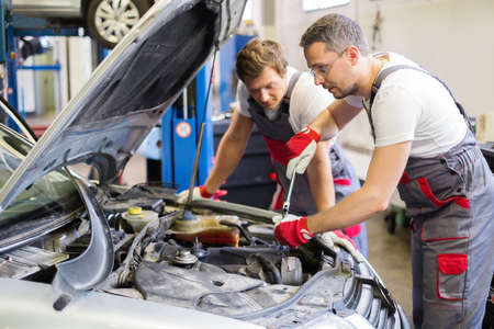 automobile workshop: Two mechanic fixing car in a workshop