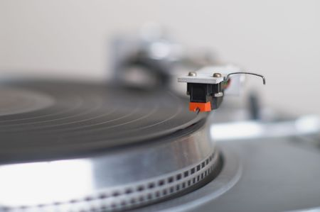 This stylish 20-years old turntable is ready to play disk. The tone-arm cartridge is in focus. You can put your logo and text on it.