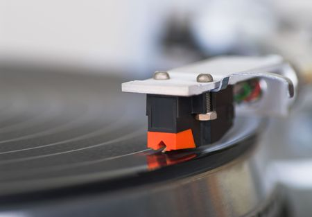 20 years old: Macro shot of 20 years old turntable tone-arm cartridge playing disk. You can put you logo on it.