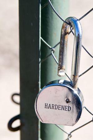 chromeplated: Broken chrome-plated hardened padlock beside open gate