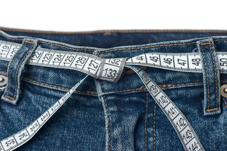 waist belt: Waist check and excess weight control concept. Pair of blue jeans with measuring tape as belt having tied knot
