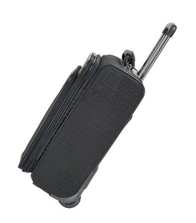 Modern stylish black travel suitcase with pullout handle tilted side view isolated on white with clipping path