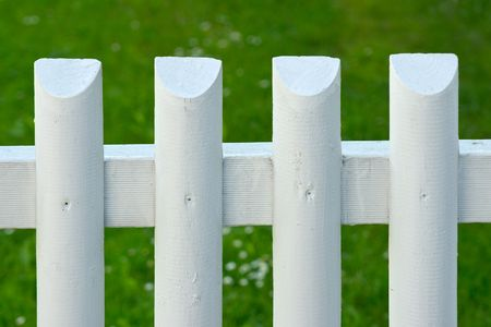 batten: White batten fence with green grass on background