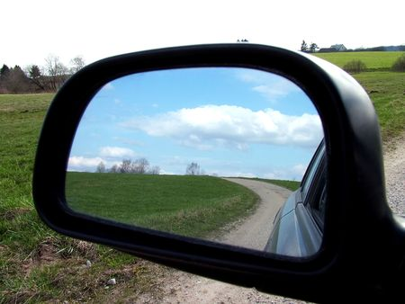 Rear view on a car mirror, road to hill