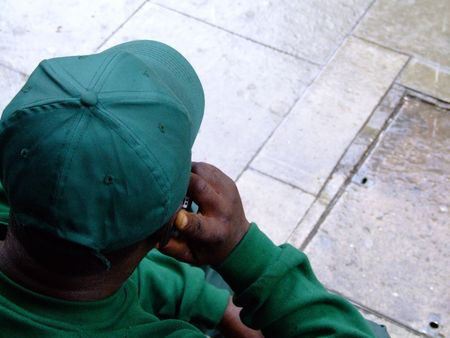 Worker in green uniform using mobile phone photo