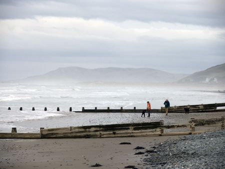people walking down a wind swept beach with mist in the background photo