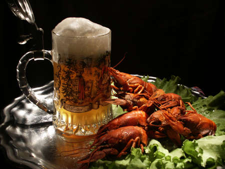 spiny lobster: Mug of beer with pucture of christmas tree. Crawfish and lettuce. All on metallic tray. Photo made with light-brush technique. Objects isolated on black background. Stock Photo