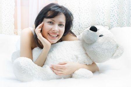 Beautiful girl in the bed with teddy-bear, smiling photo