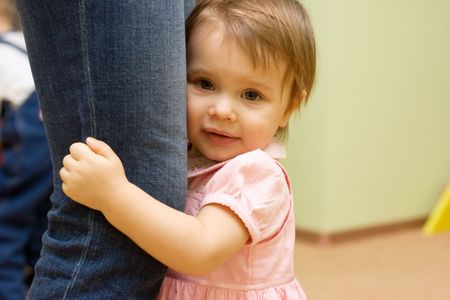 Shy cute  with mother, holding her knees Stock Photo