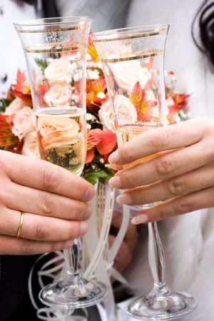 Hands of bride and groom holding two glasses of champagne. Low DOF, focus on hands photo