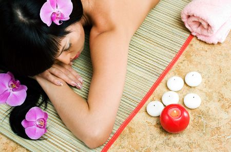 Beautiful asian girl with orchids relaxing in spa salon photo