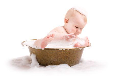 Cute baby having bath in old tub with foam