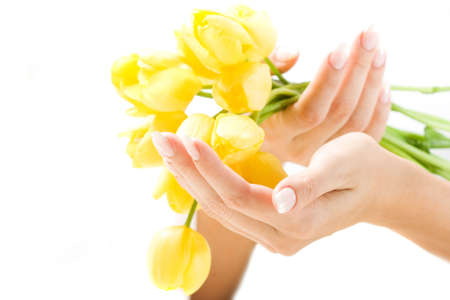 Beautiful hands with French manicure and bunch of tulips. Soft-focused, low DOF