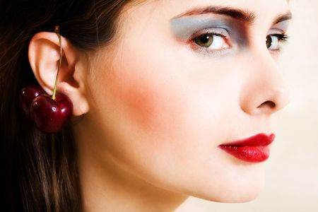 Beautiful young woman in evening make-up with cherry photo