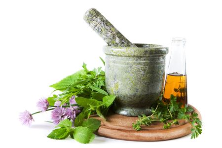 Herbs with mortar and bottle with oil photo