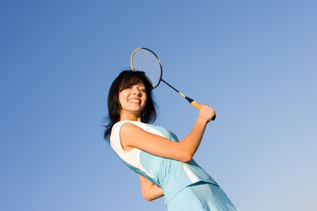 badminton racket: Young woman playing badminton on blue sky background Stock Photo