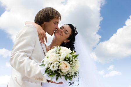 Bride and groom kissing on the blue sky background photo