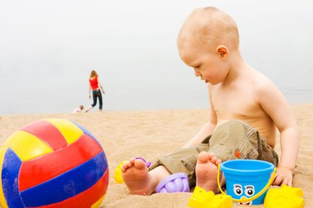 little boy playing with toys on the beach photo