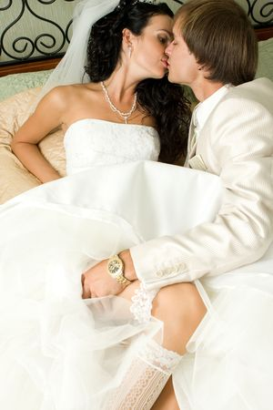 Bride and groom kissing in the bedroom photo