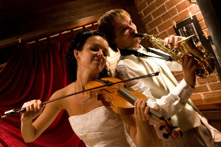 Just married. Happy couple playing music at club photo