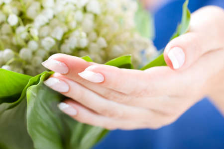 may lily: Beautiful hands with French manicure and bunch of may lily. Soft-focused, low DOF