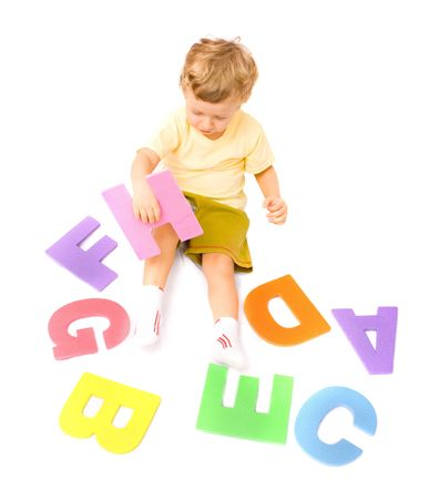 Cute little boy learning alphabet playing with letters. Isolated over white photo