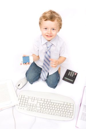 Little boy playing with cell phone, calculator and computer keyboard photo
