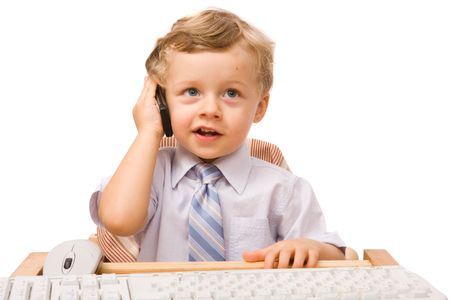 Young boy sitting at the office desk with computer and talking over cell phone photo
